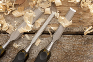 Set of three woodworking chisels lying on rustic wooden boards with fresh wood shavings in a carpentry or woodworking concept