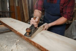 Master carpenter in shirt and apron strokes plane in workshop. Close up