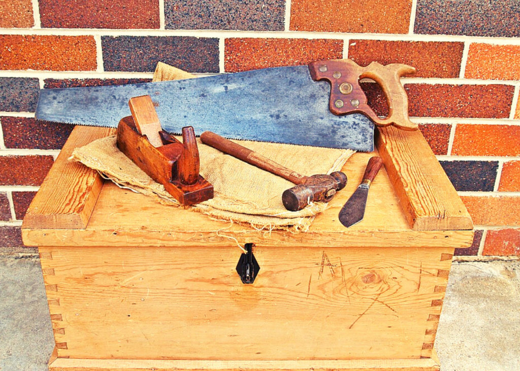 A rip saw and some tools on a tool box