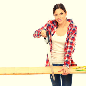 A woman using a rip saw for her woodworks